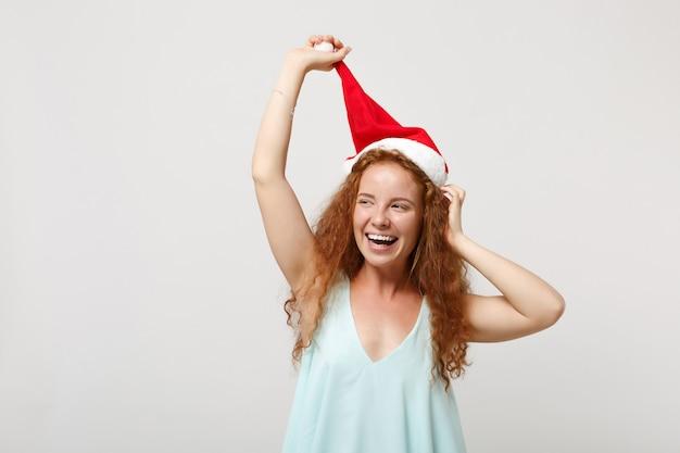 Rire jeune rousse santa girl dans des vêtements légers posant isolé sur fond de mur blanc portrait en studio. concept de vacances de célébration de bonne année 2020. maquette de l'espace de copie. tenant le chapeau de noël.