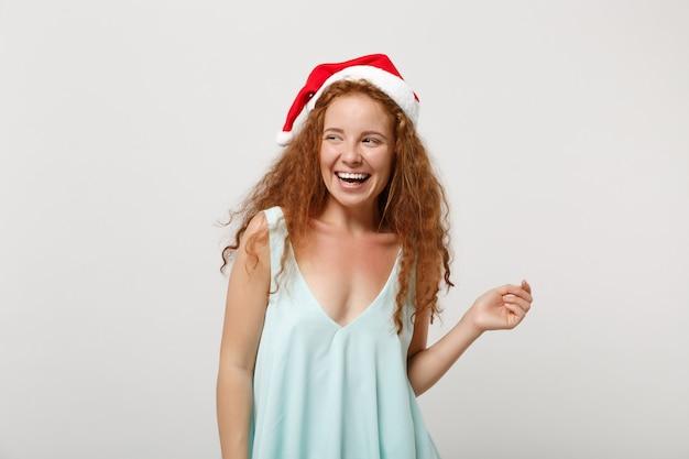 Rire jeune rousse santa girl en vêtements légers, chapeau de noël isolé sur fond blanc, portrait en studio. concept de vacances de célébration de bonne année 2020. maquette de l'espace de copie. en regardant de côté.