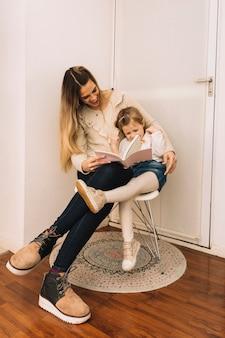 Rire mère et fille lisant un livre près de la porte
