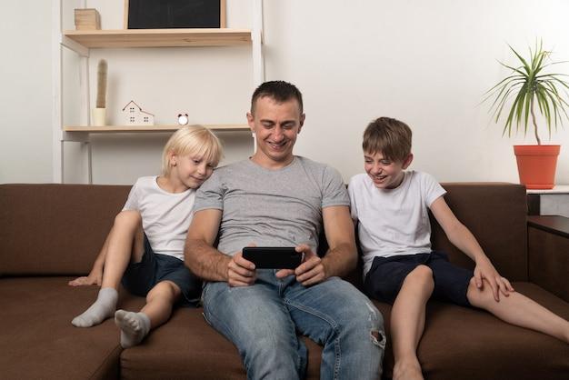 Rire papa et deux fils sont assis sur un canapé et regardent une vidéo au téléphone.