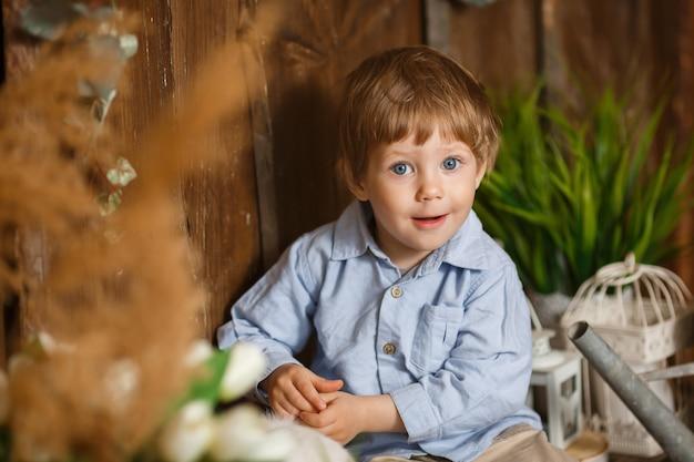 Rire petit garçon jouant avec le lapin de pâques dans une herbe verte. décoration rustique. fond en bois