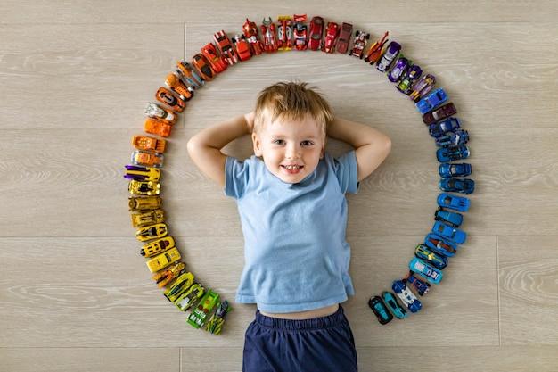Rire petit mignon petit garçon allongé dans un cercle de jouets modèle de voiture collection hot wheels vue de dessus