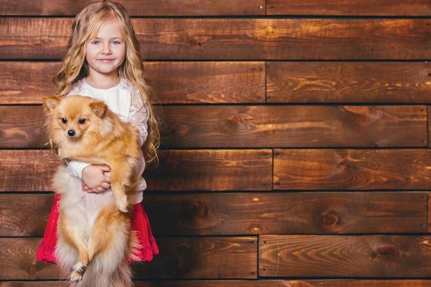 Rire petite fille aux longs cheveux blonds tient chaque chien à l'arrière-plan d'un mur en bois.