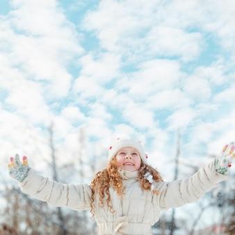 Rire de petite fille en hiver marcher sur fond de ciel de nuages.