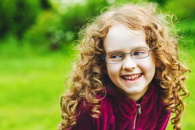 Rire de petite fille à lunettes dans le parc du printemps.