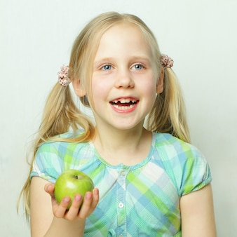Rire petite fille avec pomme verte