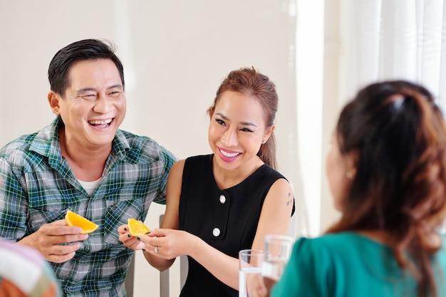 Rire positif couple vietnamien mûr mangeant des tranches d'orange au dîner avec des amis