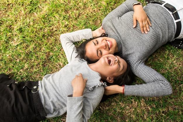 Rire sœur aînée de mère latine ou jeune baby-sitter jouant en plein air sur l'herbe avec la petite fille.