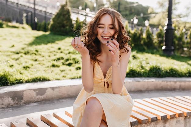 Rire spectaculaire fille de gingembre assis sur un banc en journée d'été. portrait en plein air d'une femme charmante aux cheveux roux exprimant le bonheur.