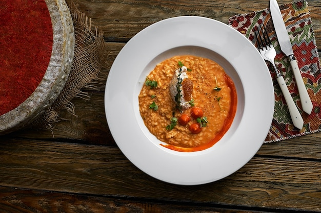 Risotto aux champignons et à la citrouille d'épeautre sur fond gris, savoureux repas végétarien.