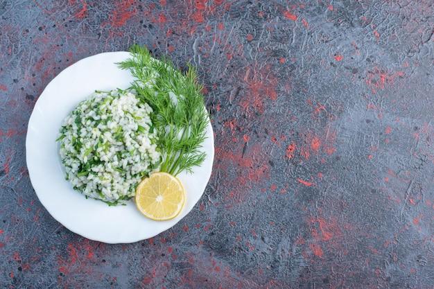 Risotto aux herbes et citron dans une assiette blanche.