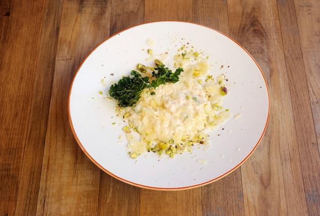 Risotto aux pistaches présenté en assiette sur fond de bois.