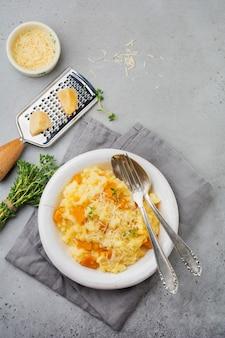 Risotto à la citrouille au thym, ail, parmesan et vin blanc sur une surface de béton gris