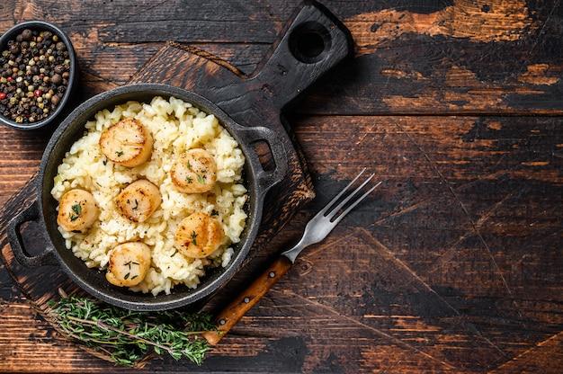 Risotto de fruits de mer aux pétoncles dans une casserole.