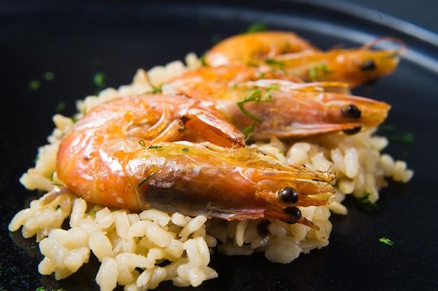 Risotto italien aux crevettes sur une assiette noire.