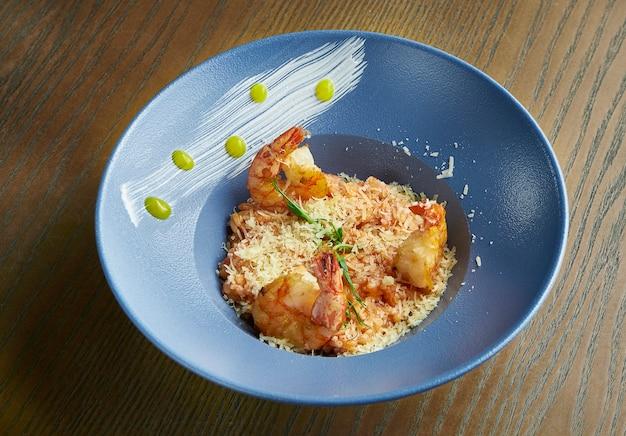 Risotto de riz aux crevettes. riz aux fruits de mer dans un bol bleu contre un bois. cuisine italienne