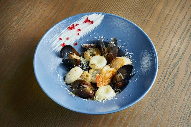 Risotto de riz noir aux crevettes, moules et pétoncles. riz aux fruits de mer dans un bol bleu contre un bois.