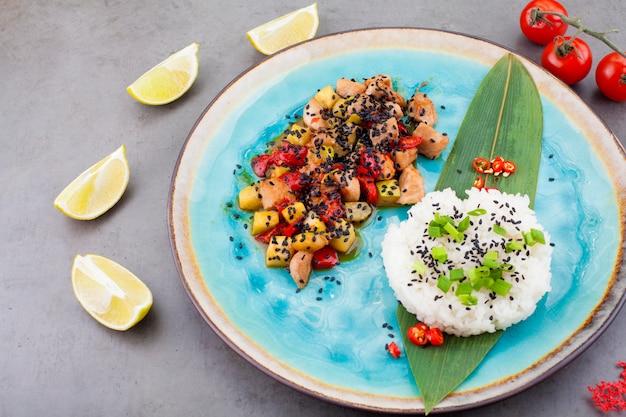 Risotto, riz servi sur une feuille de palmier à côté d'une garniture de légumes et de viande, sur fond gris, à côté de tranches de citron vert et de tomates cerises. le concept de recettes ou de menus