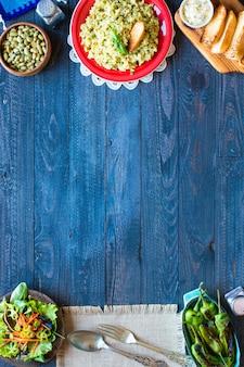 Risotto végétarien avec divers légumes, sur une table rustique en bois.