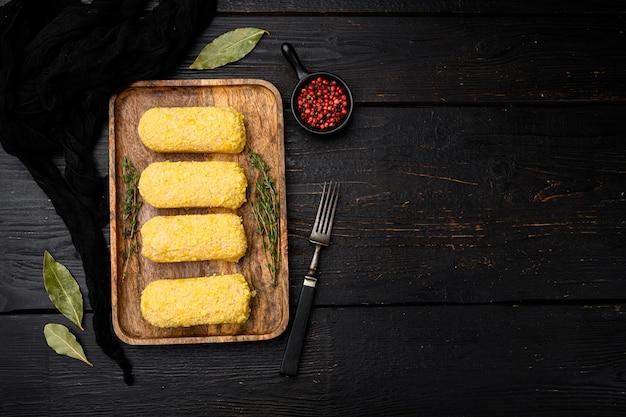 Rissoles de poulet et ensemble d'ingrédients, sur fond de table en bois noir, vue de dessus à plat, avec espace de copie pour le texte
