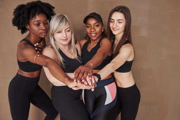 Rituel pré-entraînement. groupe de femmes multiethniques debout contre l'espace brun