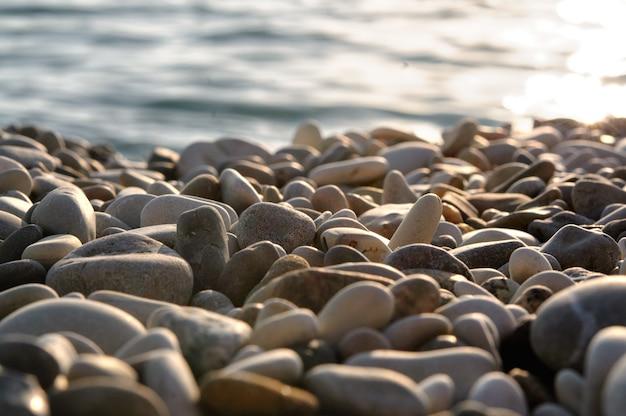 Rivage de gravier de mer ou plage d'eau de mer au coucher du soleil