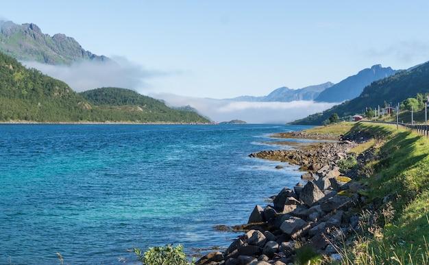 Rivage pierreux de la baie bleue contre les montagnes dans le brouillard, lofoten, norvège