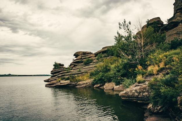 Rivage rocheux sur le lac par temps nuageux.