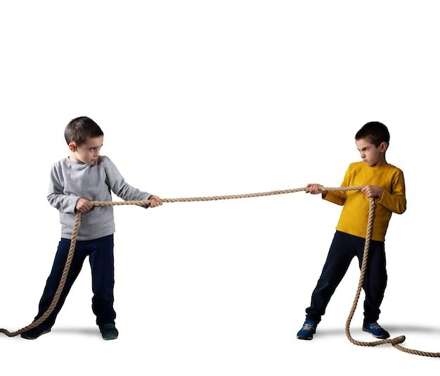 Rivalité de deux frères qui ont un concours avec une corde isolée sur blanc