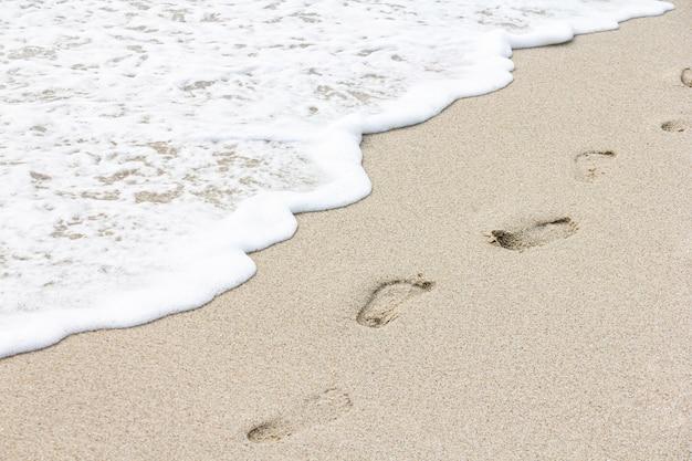 Rive de la plage avec des empreintes de pas en temps nuageux