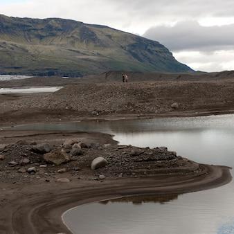 Rive rocheuse du lac glaciaire avant les montagnes lointaines
