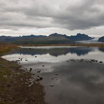 Rive rocheuse du lac glaciaire, des montagnes et des glaciers à distance