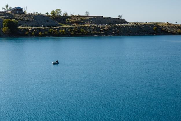 Rive sud du lac issyk-kul au kirghizistan, pêcheur solitaire sur un bateau sur le lac issyk-kul