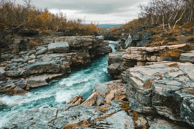 Rivière agitée qui coule dans le canyon du parc national d'abisko en suède polaire