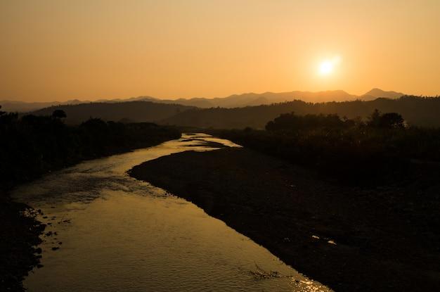 Rivière et ciel coucher de soleil. image de silhouette de la rivière et les montagnes dans le fond de la soirée.