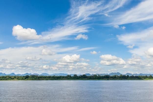 Rivière et cirrus, cumulus sur fond de ciel bleu.