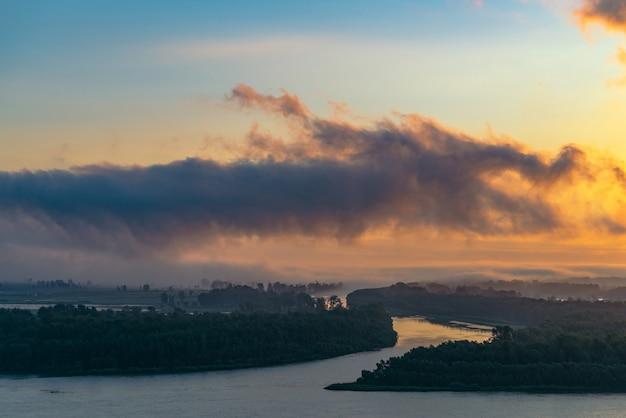 La rivière coule le long du rivage avec une forêt sous le brouillard.