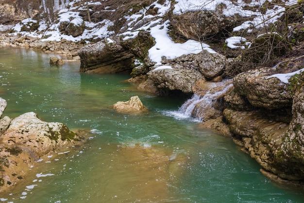 Rivière dans les montagnes. zone montagneuse. photo sur une longue exposition, jour nuageux. cascades dans les montagnes dans la forêt, paysage hivernal des rivières de montagne