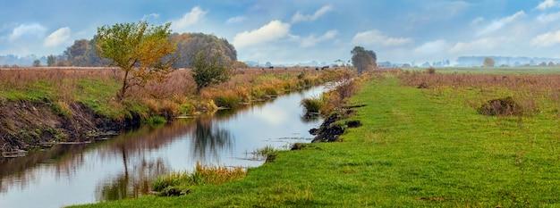 Rivière étroite parmi un vaste champ à l'état sauvage