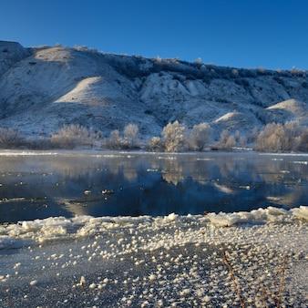 Rivière gelée depuis les rives vallonnées et les grandes banquises. une journée ensoleillée avec un ciel sans nuages.