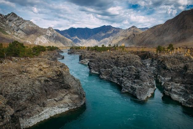 La rivière katun turquoise dans les gorges est entourée de hautes montagnes sous un ciel d'automne majestueux. un ruisseau de montagne orageux coule parmi les rochers - paysage des montagnes de l'altaï, de beaux endroits de la planète