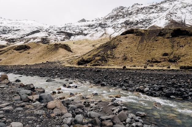 Rivière de montagne au pied de la montagne avec une herbe sèche jaune de pointe enneigée sur les montagnes