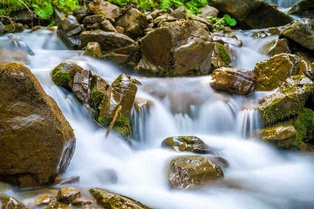 Rivière de montagne avec petite cascade aux eaux turquoises claires tombant entre des rochers humides avec une épaisse mousse blanche.