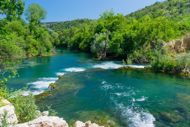 Une rivière de montagne rapide coule à travers les rapides.