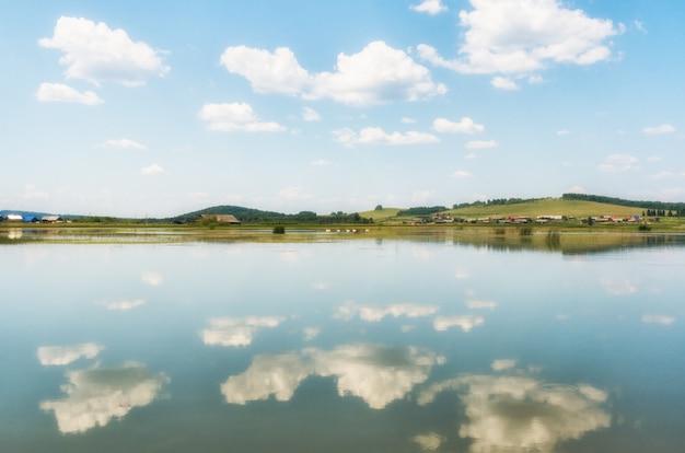 La rivière, petit village derrière elle et ciel bleu avec des nuages, se reflétant dans l'eau.