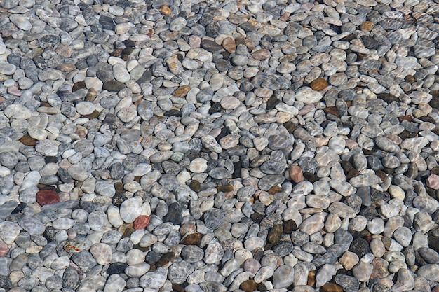 Rivière de pierre en fond de texture d'eau claire, gros plan de la surface de la roche