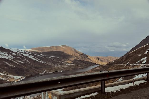 Rivière qui coule entourée par les hautes montagnes couvertes de neige en hiver