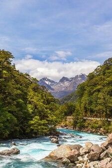 Rivière rapide sur fond de montagnes parc national de fiordland nouvelle-zélande