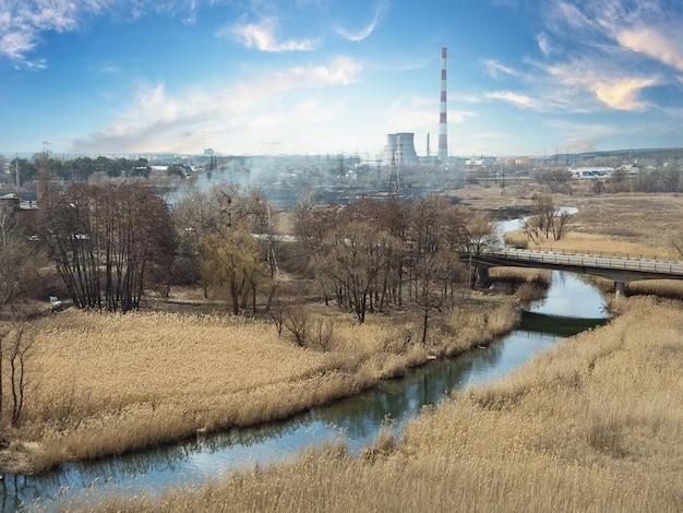 Rivière avec des roseaux secs le long des berges sur fond de tuyaux de centrale électrique