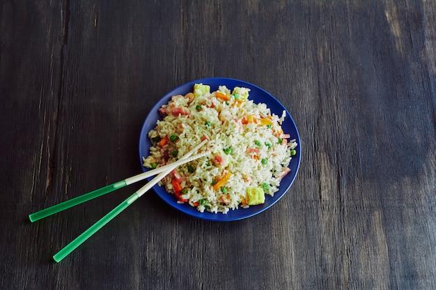 Riz 3 délices dans un plat en fibre de bambou avec bâtons de résine